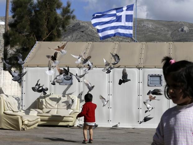 Crianças brincam em um pequeno campo de refugiados no porto de Pothia, na ilha grega de Kalymnos, e fazem pombos levantarem voo em frente a uma bandeira da Grécia (Foto: Thanassis Stavrakis/AP)