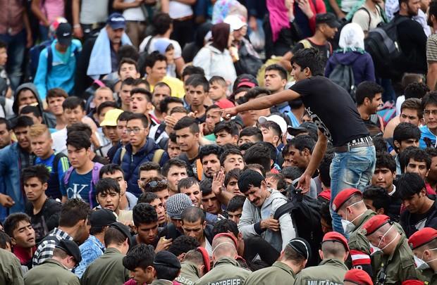 Refugiados se aglomeram na fronteira húngara com a Áustria e esperam para partir em direção a Alemanha  (Foto: Attila Kisbenedek/AFP)