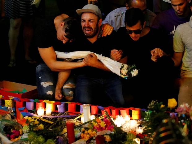 Homens se abraçam e dão as mãos emocionados durante vigília à luz de velas em memória às vítimas do atirador na boate gay Pulse, em Orlando, na Flórida (EUA) (Foto: Carlo Allegri/Reuters)