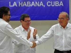 O comandante das Farc Iván Marquéz (esquerda) e o chefe da delegação de paz colombiana Humberto de la Calle (direita) apertam as mãos em Havana, Cuba, após acordo de paz na Colômbia (Foto: Yamil Lage / AFP Photo)