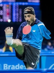 Descrição da imagem: Ibrahim Hamadtou levanta a bola de tênis de mesa com o pé para sacar com a raquete segura pela boca (Foto: Divulgação/ITTF)