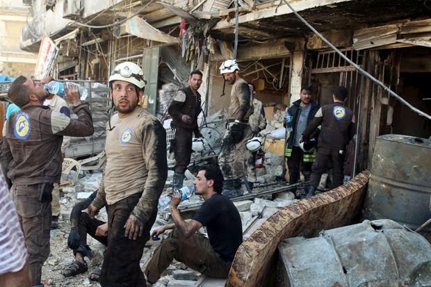 Socorristas descansam em meio aos escombros de edifícios danificados após um ataque aéreo no bairro de Tariq al-Bab, que é controlado pelos rebeldes em Aleppo, na Síria (Foto: Abdalrhman Ismail/Reuters)