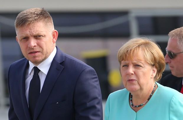 Primeiro-ministro eslovaco, Robert Fico, com a chanceler alemã, Angela Merkel, na sexta-feira (16) (Foto: Yves Herman/Reuters)