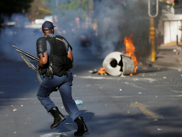 Policial corre para passar por barricada durante confronto com estudantes em universidade, em Joanesburgo, na África do Sul (Foto: Siphiwe Sibeko/ Reuters)