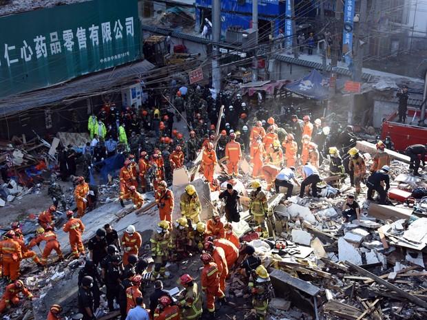 Equipe de resgate busca sobreviventes entre destroços após o desabamento de quatro prédios em Wenzhou, na província de Zheijang, na China, durante as primeiras horas do dia. No mínimo quatro pessoas morreram no local, segundo autoridades (Foto: AFP/Stringer)