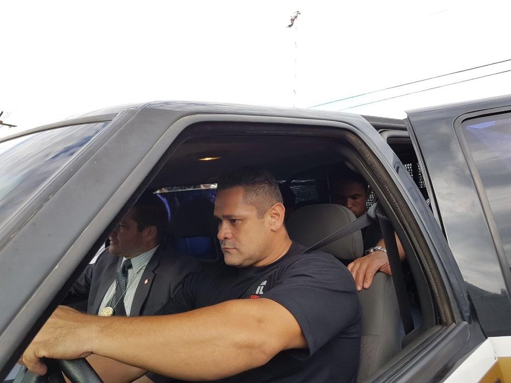No banco de trás da viatura da polícia, Bruno chega ao presídio de Varginha (Foto: Samantha Silva / G1)
