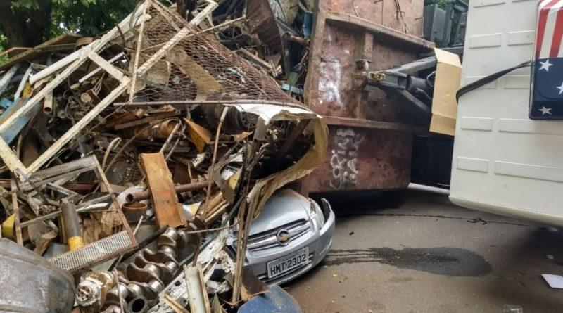 Caminhão carregado com sucatas tomba sobre carro em Varginha